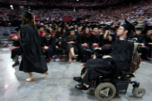 soon-to-be graduate navigates his wheelchair toward the stage at Commencement
