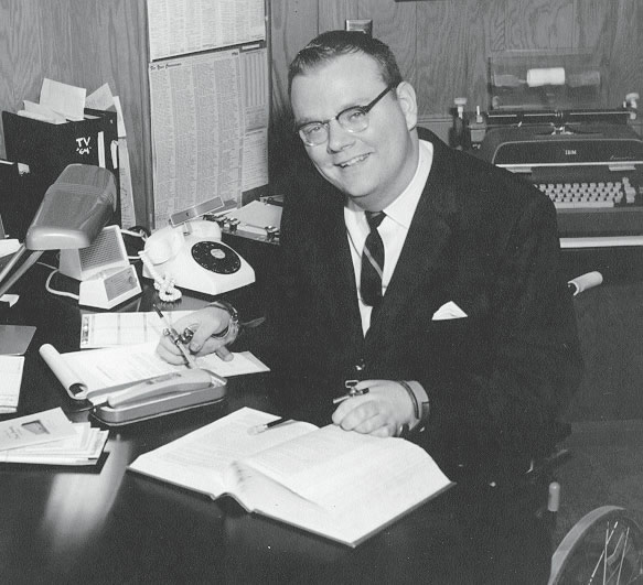 Mike McBurney reading and writing at his office desk in 1960s