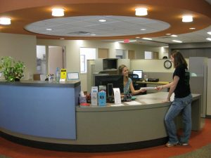 Student submitting paper document at the McBurney Center front desk