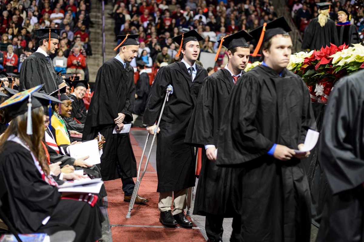 Graduate walking in a line using crutches in 2015 graduation ceremony